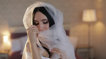 подвенечное платье : Beautiful and lovely brunette bride in night gown and veil. Close-up shot. Pretty and well-groomed woman sitting on a bed. Wedding morning. Slow motion