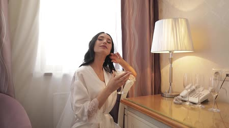 evli : Beautiful and lovely bride in night gown and veil with glass of martini. Pretty and well-groomed woman sitting on a chair in hotel room. Wedding morning. Slow motion Stok Video
