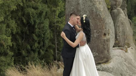 новобрачный : Beautiful bride with groom standing on the mountain hills. Hugs. Wedding couple. Happy family. Man and woman in love. Lovely groom and bride. Wedding day. Slow motion