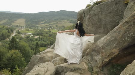 новобрачный : Beautiful and lovely bride in wreath of flowers standing on the mountain hills. Pretty and well-groomed woman in love. Wedding day. Slow motion