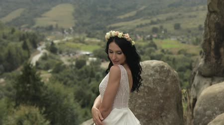 çelenk : Beautiful and lovely bride in wreath of flowers standing on the mountain hills. Pretty and well-groomed woman in love. Wedding day. Slow motion