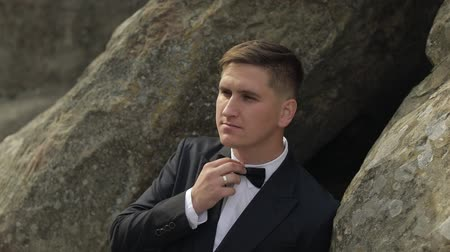 новобрачный : Handsome groom standing on the mountain hills. Fixes his bow tie. White shirt with black bow tie. Wedding day. Businessman. Slow motion