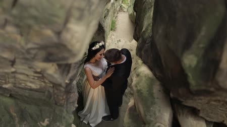 новобрачный : Groom with bride standing in cave of mountain hills. Hugs. Wedding couple. Happy family. Man and woman in love. Lovely groom and bride. Wedding day. View from top. Slow motion Стоковые видеозаписи