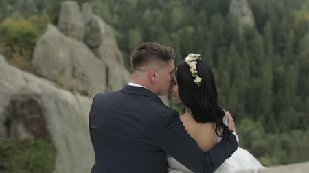 новобрачный : Beautiful bride with groom sitting on the mountain hills. Hugs. Wedding couple. Happy family. Man and woman in love. Lovely groom and bride. Wedding day. Slow motion Стоковые видеозаписи