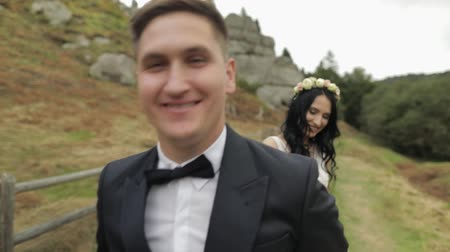 новобрачный : Beautiful bride with groom walking near mountain hills. Hugs. Wedding couple. Happy family. Man and woman in love. Lovely groom and bride. Wedding day. Slow motion