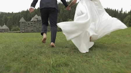 новобрачный : Beautiful bride with groom running near forest. View from behind. Wedding couple. Happy family. Man and woman in love. Lovely groom and bride. Wedding day. Slow motion