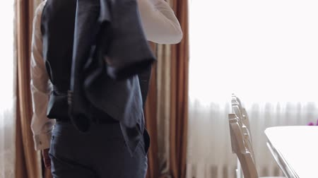 smokin : Handsome groom takes a jacket from a chair and goes to the window. Wedding morning. Businessman. Close-up shot. Slow motion