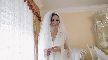 новобрачный : Beautiful and lovely bride in night gown and veil. Pretty and well-groomed woman stay near window. Wedding morning. Slow motion