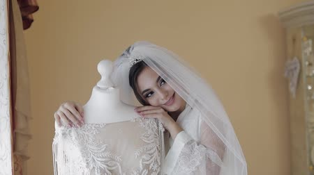 camisola : Beautiful and lovely bride in night gown and veil near wedding dress on a manicure. Pretty and well-groomed woman in nightdress. Wedding morning. Slow motion