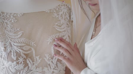 preparált : Beautiful and lovely bride in night gown and veil near wedding dress on a manicure. Pretty and well-groomed woman in nightdress. Wedding morning. Slow motion