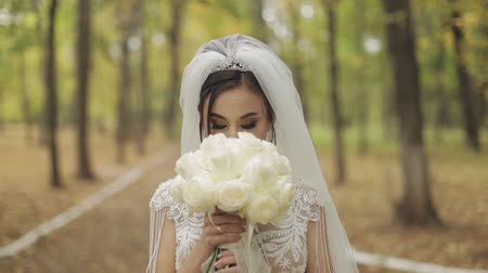 tırnak : Wedding bouquet in the hands of the bride. Wedding day in the park. Engagement. Pretty and well-groomed woman n the park. Slow motion