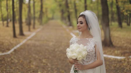 závoj : Wedding bouquet in the hands of the bride. Wedding day in the park. Engagement. Pretty and well-groomed woman n the park. Slow motion