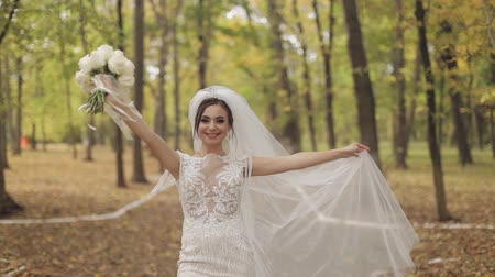 tırnak : Wedding bouquet in the hands of the bride. Wedding day. Bring walking in the park. Engagement. Pretty and well-groomed woman n the park. Slow motion