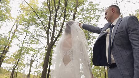 veli : Lovely young caucasian bride and groom in the park. Wedding couple. Happy family. Newlyweds. Man and woman in love. Slow motion Filmati Stock