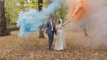 nowożeńcy : Lovely young caucasian bride and groom walking in the park with multi-colored smoke bombs. Wedding couple. Happy family. Newlyweds. Man and woman in love. Slow motion