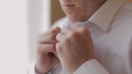 vlinderdas : Groom fixes his white shirt. Standing near window. Wedding morning. Businessman. Close-up shot. Portrait. Slow motion