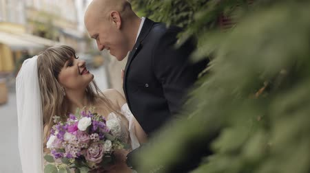 nowożeńcy : Newlyweds in the center of the town. Lovely young caucasian bride and groom. Wedding couple. Happy family. Man and woman in love. Slow motion