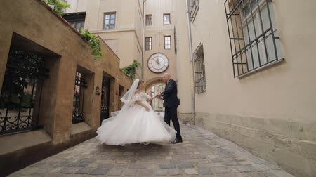 lviv : Newlyweds dance in the center of the old city. Lovely young caucasian bride and groom. Wedding couple. Happy family. Man and woman in love. Slow motion