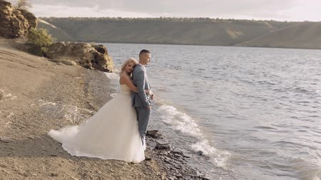 невеста : Newlyweds stand on the riverbank. The bride hugs the groom. Wedding couple. Happy family. Man and woman in love. Wedding day. Slow motion Стоковые видеозаписи
