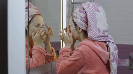 melisa : Woman applying cosmetic face mask and looking at mirror in bathroom. Girl taking care of her face skin. Skincare spa treatment. Facial mask