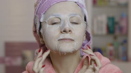 melisa : Woman applying cosmetic face mask and looking at camera in bathroom. Girl taking care of her face skin. Skincare spa treatment. Facial mask Stok Video