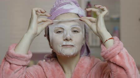 hidrasyon : Woman applying cosmetic face mask and looking at camera in bathroom. Girl taking care of her face skin. Skincare spa treatment. Facial mask Stok Video