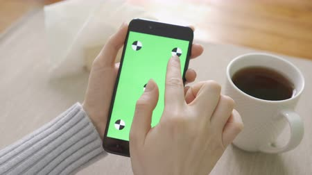 coffee house : Close-up of woman who are sitting indoors and watching photographs on the mobile devices green screen.Green screen Chroma Key. Close up. Tracking motion. Stock Footage