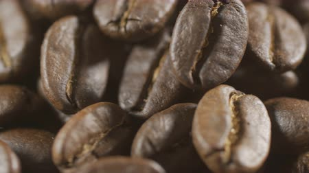 americano : Whirling coffee grains background. Barista preparing fresh roasted coffee beans for making espresso. Morning black coffee texture. Close-up rotation of the heap of coffee beans.