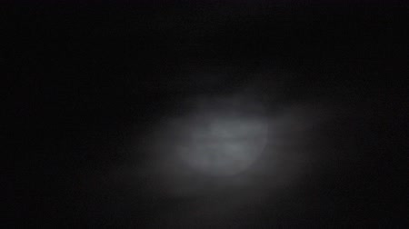 teleskop : Time lapse of an extreme large full moon as it rises in the bight sky with black clouds in its foreground Stok Video