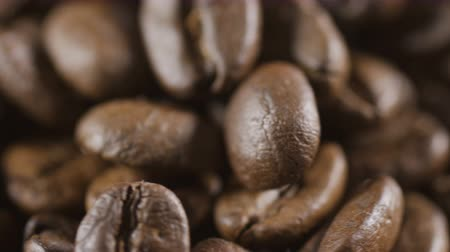 rotational : Coffee beans in extreme close up background stock footage. Coffee beans in macro close up with Coffee granules background.