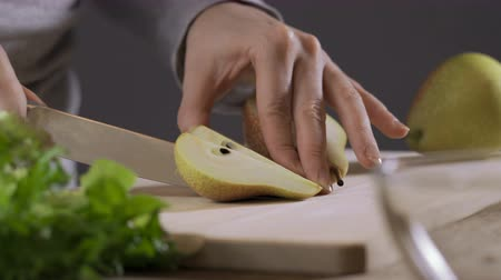 tábua de cortar : woman cuts a pear on a wooden board.