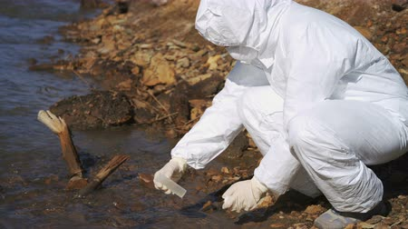 bad ecology : Bbiologist in biohazard suits and masks sampling water from a river for chemical analysis Stock Footage