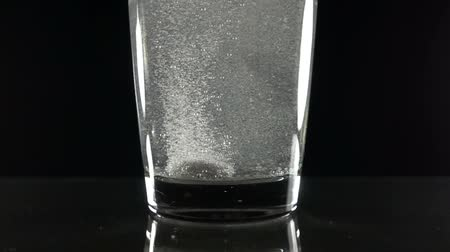 oldódó : Effervescent vitamin C tablet bubbles in glass of water. Pill in slow motion close up. Stock mozgókép