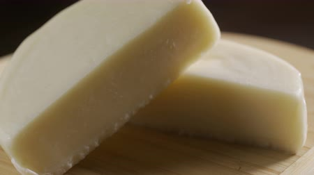 emmental : cheese, cut into half on a wooden plate. Rotates against a gray background