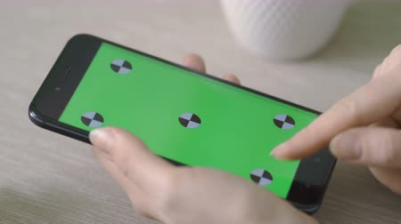 tur : Woman Using Phone with Green Screen. Easy for tracking and keying.