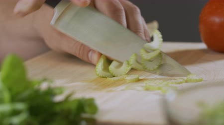 zeller : hand of an expert chef cuts celery