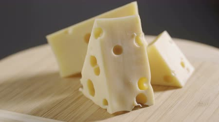 rokfort : cheese, cut into pieces on a wooden plate. Rotates against a gray background