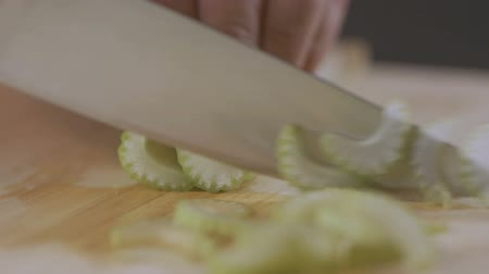 zeller : Macro shot of celery being sliced on wooden chopping board. Stock mozgókép