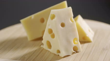 коровы : Rotation cheese on wooden plate. Delicious cheese Maasdam on the cutting board on gray background Стоковые видеозаписи
