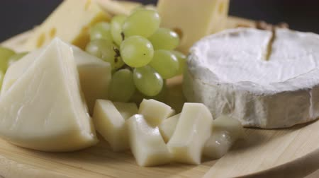 toalha : Cheese platter with different cheese and grapes