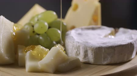 sýr : Honey is poured onto a cheese plate with different cheeses, grapes and nuts. Perfectly suited to wine, delicacy