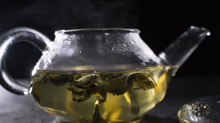 мята : Tea brewing. Green tea leaves swirling in a glass pot.