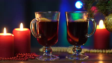 tarçın : Two glasses of mulled wine stand on a blurred background of a Christmas tree, colorful Christmas lights and red candles Stok Video