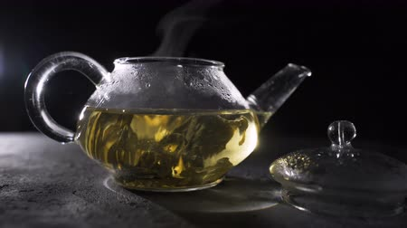 cseppfolyósítás : Green tea is brewed in a glass teapot on a black background.