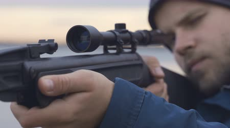 eye piece : man in a black hood charges a rifle, takes aim and makes a shot, close-up Stock Footage