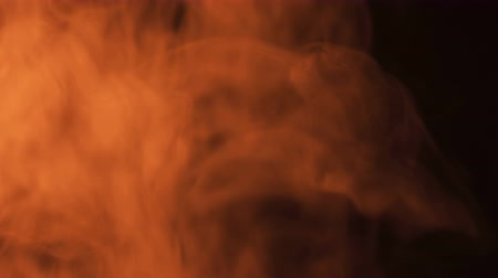 dumanlı : Puffs of orange smoke on a black background, illuminated by fire. Stok Video