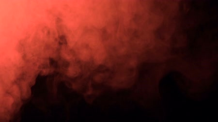 escape : puffs of red smoke in super slow motion appearing against a black background