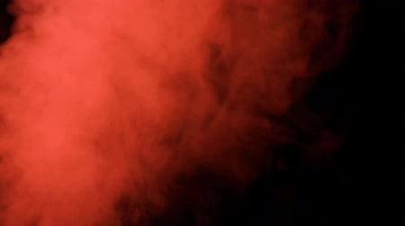 gunshot : puffs of red smoke in super slow motion appearing against a black background