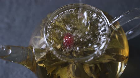 demlik : Tea brewing. Dry tea leaves with boiling water flooded. Green tea leaves swirling in a glass pot.