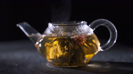 brew tea : Tea brewing. Dry tea leaves with boiling water flooded. Green tea leaves swirling in a glass pot.